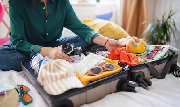 Jeune femme méconnaissable avec une valise pour des vacances à la maison, concept de coronavirus.