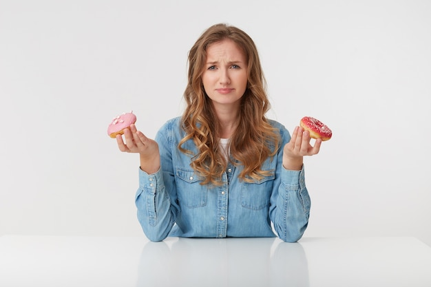 Jeune femme mécontente aux longs cheveux blonds ondulés, assise à la table et tient des beignets dans ses mains. froncer les sourcils, regardant avec dégoût à la caméra isolée sur fond blanc.