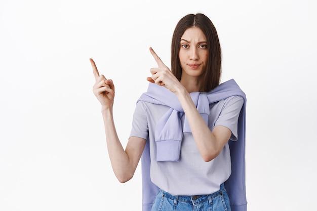 Une jeune femme mécontente demande des réponses, pointant vers le coin supérieur gauche et a l'air critique, déçue, debout sur un mur blanc