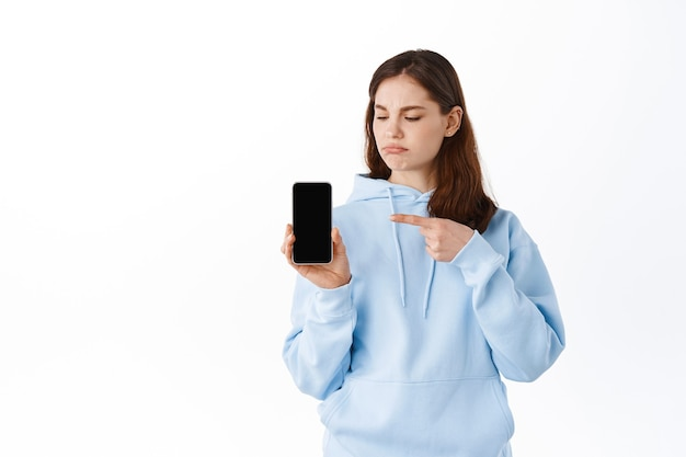 Jeune femme mécontente montrant une mauvaise application sur son téléphone, pointant vers un écran de smartphone vide et grimaçant contrarié, debout contre un mur blanc