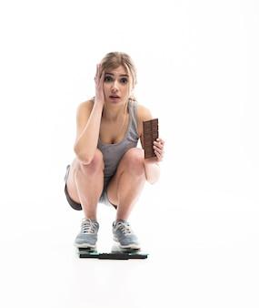 Jeune femme mécontente de son poids tenant du chocolat, isolé sur blanc.
