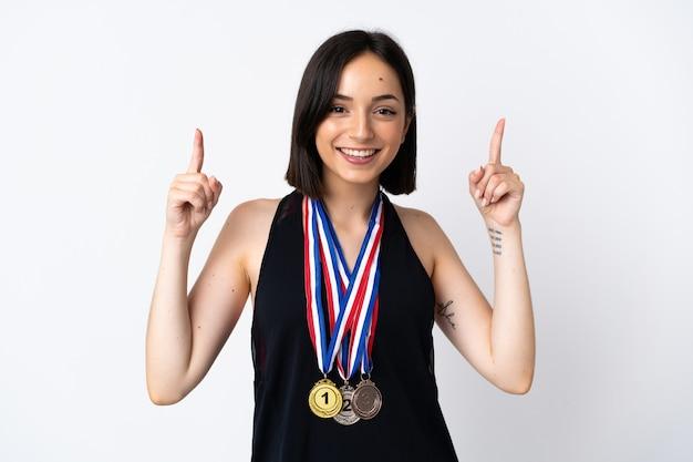 Jeune femme avec des médailles isolé sur blanc pointant vers le haut une excellente idée