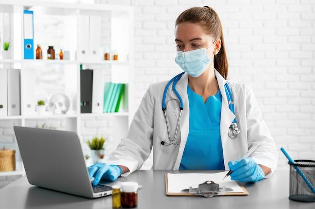 Jeune femme médecin assis à la table de travail à l'aide d'un ordinateur portable se bouchent