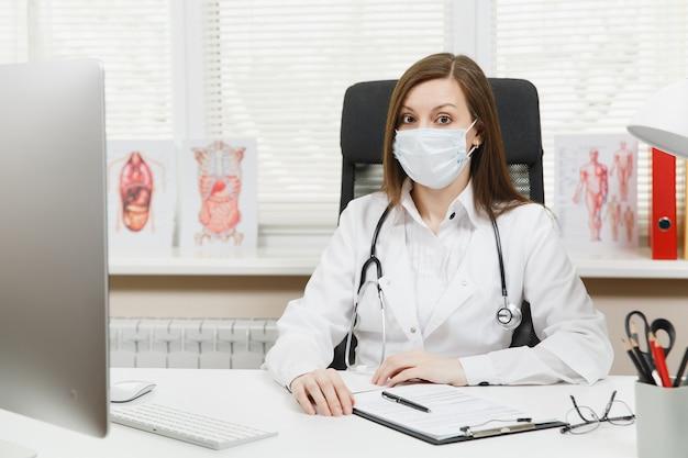 Jeune femme médecin assise au bureau, travaillant sur un ordinateur moderne avec des documents médicaux dans un bureau léger à l'hôpital