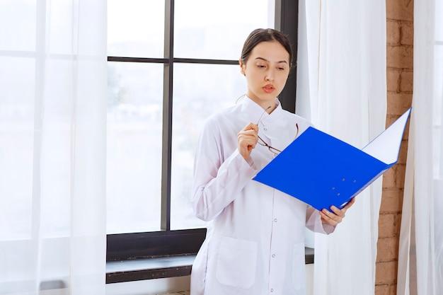 Jeune femme médecin en blouse blanche lisant sur le prochain patient près de la fenêtre.