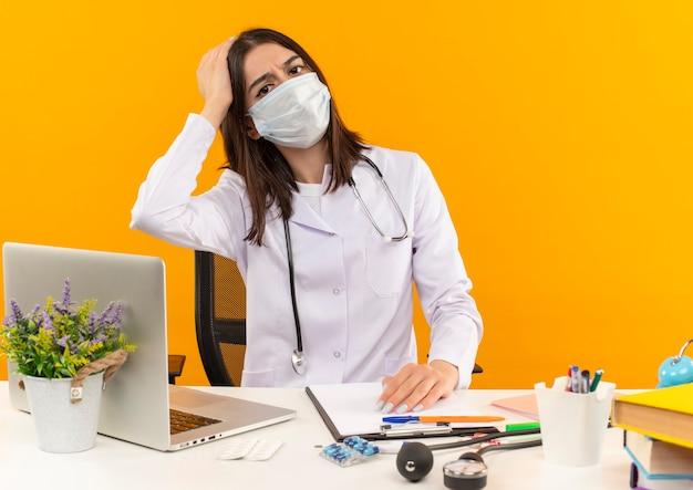 Jeune femme médecin en blouse blanche et masque de protection du visage avec stéthoscope à l'avant confus assis à la table avec un ordinateur portable et des documents sur un mur orange
