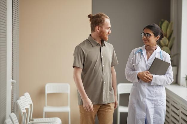 Jeune femme médecin en blouse blanche parlant à un patient de sexe masculin pendant qu'ils marchent le long du couloir à l'hôpital