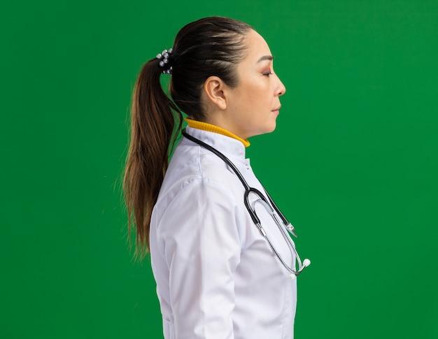 Jeune femme médecin en blouse blanche avec stéthoscope autour du cou debout sur le côté avec le visage serioys sur le mur vert