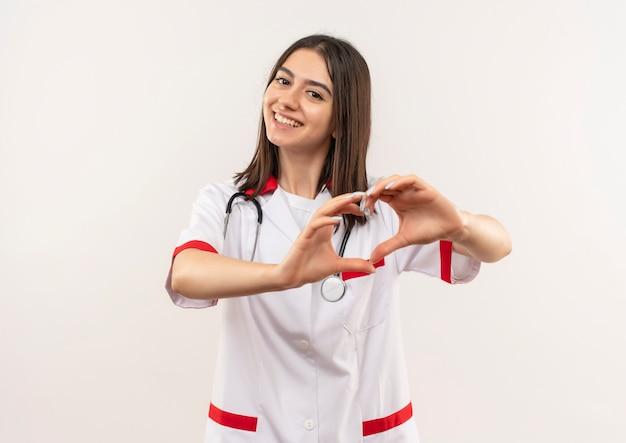 Jeune femme médecin en blouse blanche avec un stéthoscope autour du cou montrant le geste du cœur souriant sympathique debout sur un mur blanc
