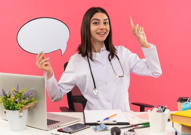 Jeune femme médecin en blouse blanche avec un stéthoscope autour du cou tenant un signe de bulle de dialogue vierge pointant vers le haut avec le doigt assis à la table avec un ordinateur portable sur un mur rose