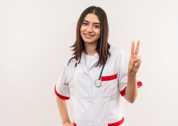 Jeune femme médecin en blouse blanche avec stéthoscope autour de son cou montrant et pointant vers le haut avec les doigts numéro deux souriant debout sur un mur blanc
