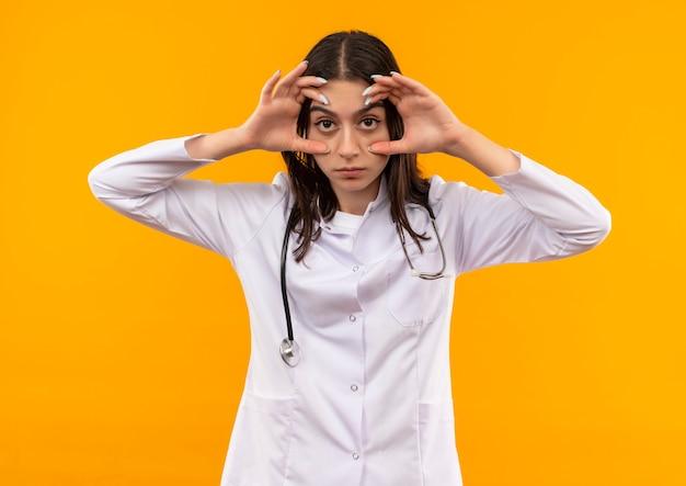 Jeune femme médecin en blouse blanche avec stéthoscope autour de son cou ouverture des yeux avec les doigts sensation de fatigue matinale debout sur un mur orange