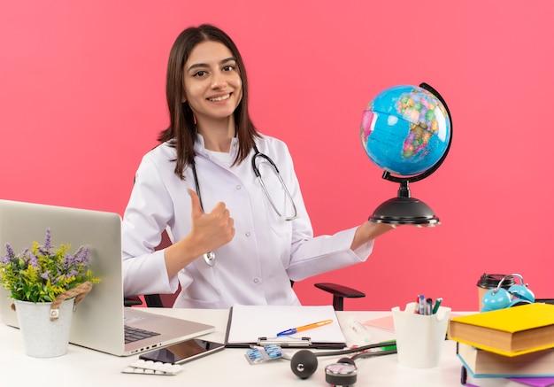 Jeune femme médecin en blouse blanche avec stéthoscope autour de son cou tenant le globe à l'avant avec le sourire sur le visage montrant les pouces vers le haut assis à la table avec un ordinateur portable sur un mur rose