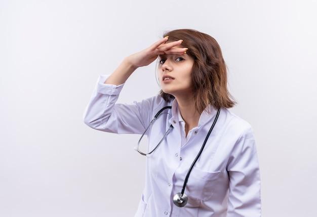 Jeune femme médecin en blouse blanche avec stéthoscope à l'esprit lointain la main sur la tête pour regarder quelqu'un ou quelque chose
