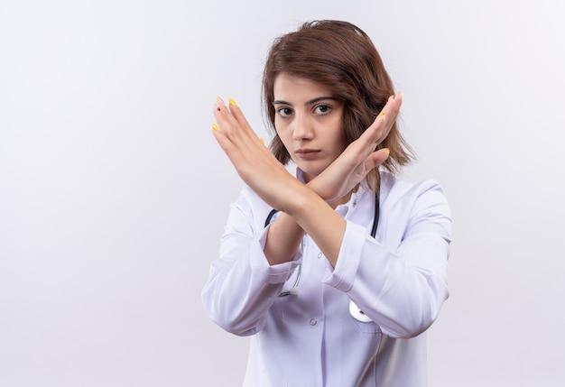 Jeune femme médecin en blouse blanche avec stéthoscope faisant le geste de défense croisant les bras sur le visage debout sur mur blanc