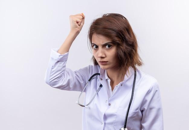 Jeune femme médecin en blouse blanche avec stéthoscope levant le poing avec le visage en colère debout sur un mur blanc