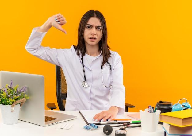 Jeune femme médecin en blouse blanche avec stéthoscope à mécontent montrant les pouces vers le bas assis à la table avec ordinateur portable et documents sur mur orange