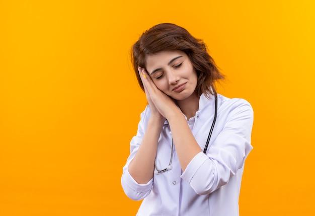 Jeune femme médecin en blouse blanche avec stéthoscope tenant les paumes ensemble la tête penchée sur les paumes veut dormir