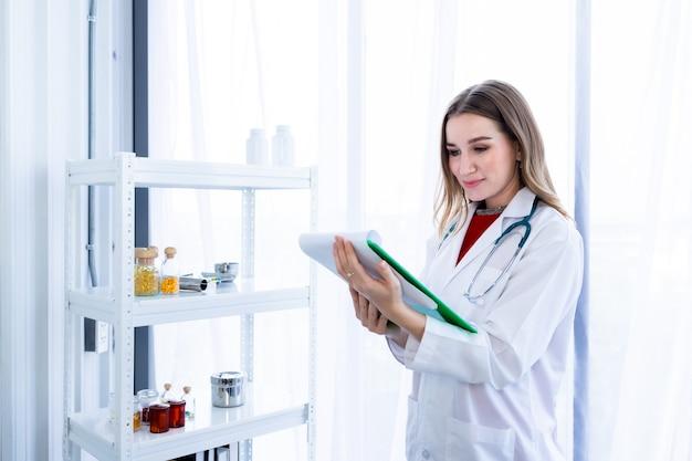 Jeune femme médecin conseillant thérapeutique avec des émotions positives tenir le presse-papiers avec un visage souriant très bien sur une table en bois à l'arrière-plan de l'hôpital