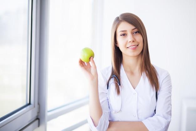 Jeune femme médecin dans une clinique moderne tenant une pomme