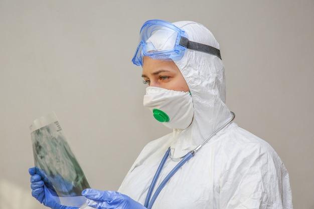 Une jeune femme médecin dans une combinaison de protection et un masque se penche sur une radiographie