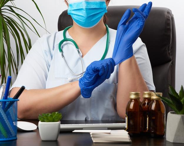 Jeune femme médecin dans un uniforme bleu, masque médical jetable est assis sur une chaise à la table et met sur ses mains des gants en latex stérile bleu