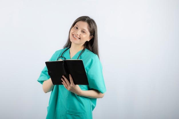 Jeune femme médecin debout avec un cahier et un crayon.