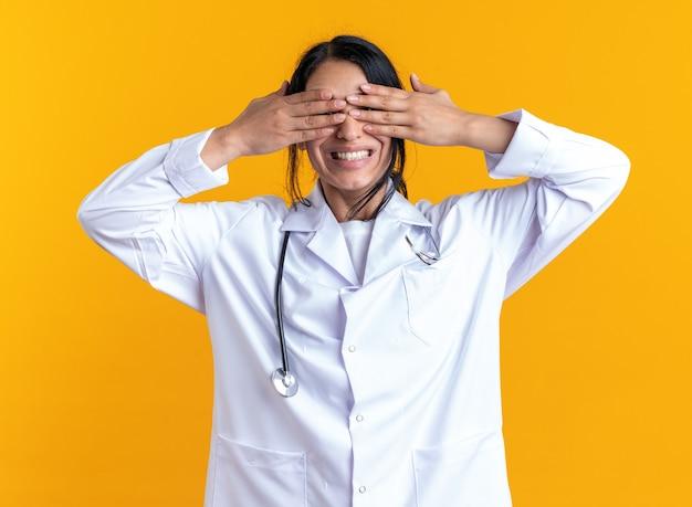 Jeune femme médecin excitée portant une robe médicale avec un œil couvert de stéthoscope avec des mains isolées sur un mur jaune