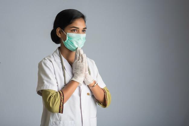 Jeune femme médecin faisant namaste à cause de l'épidémie de covid-19. nouveau message d'accueil pour éviter la propagation du coronavirus au lieu de le saluer avec un câlin ou une poignée de main.