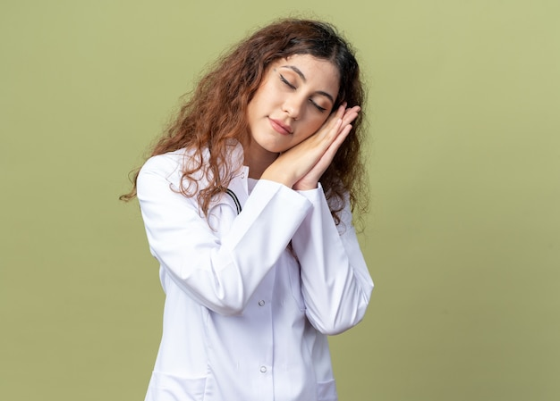 Jeune femme médecin fatiguée portant une robe médicale et un stéthoscope faisant un geste de sommeil avec les yeux fermés isolé sur un mur vert olive avec espace de copie