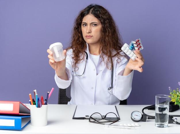 Jeune femme médecin fronçant les sourcils portant une robe médicale et un stéthoscope assis à table avec des outils médicaux regardant à l'avant tenant des pilules médicales et un bécher médical isolé sur un mur violet