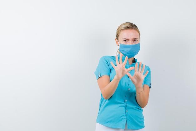 Jeune femme médecin gardant la main pour se défendre en uniforme et ayant l'air effrayée isolée