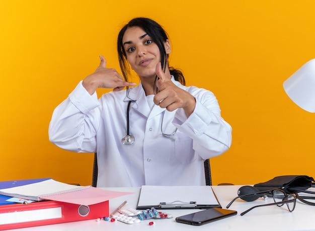 Une jeune femme médecin heureuse portant une robe médicale avec un stéthoscope est assise à table avec des outils médicaux montrant un geste d'appel téléphonique et pointe vers la caméra isolée sur un mur jaune