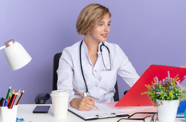 Une jeune femme médecin heureuse portant une robe médicale avec un stéthoscope est assise à table avec des outils médicaux tenant et regardant un dossier isolé sur un mur bleu