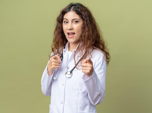 Jeune femme médecin impressionnée portant une robe médicale et un stéthoscope debout en vue de profil vous faisant un geste isolé sur un mur vert olive avec espace de copie