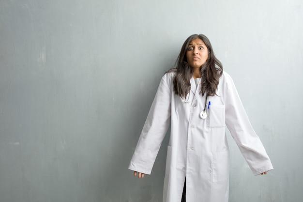Jeune femme médecin indienne contre un mur doutant et haussant les épaules, concept d'indécision et d'insécurité, incertain de quelque chose