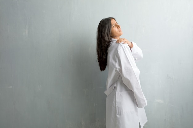 Jeune femme médecin indienne contre un mur avec maux de dos dus au stress au travail, fatigués et astucieux
