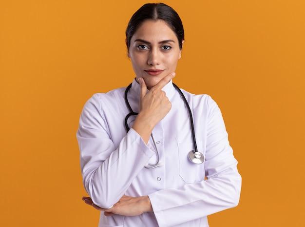 Jeune femme médecin en manteau médical avec stéthoscope autour du cou à l'avant avec une expression confiante sérieuse debout sur un mur orange