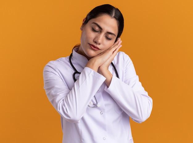 Jeune femme médecin en manteau médical avec stéthoscope faisant le geste de sommeil tenant les paumes ensemble se penchant la tête sur les paumes debout sur le mur orange