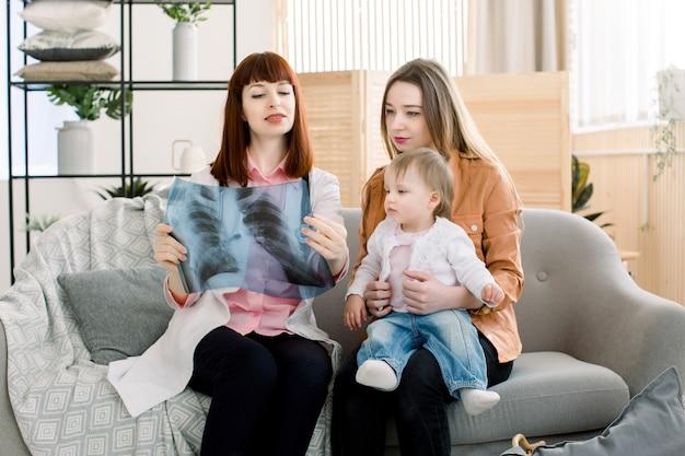 Jeune femme médecin montrant l'image xray à la jeune mère avec une fille joyeuse en clinique