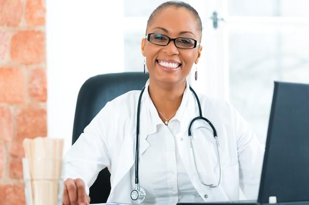 Jeune femme médecin noire assise à une fenêtre en clinique, elle a un stéthoscope