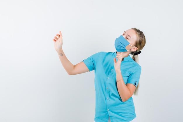 Jeune femme médecin pointant vers le haut tout en fermant les yeux en uniforme et en ayant l'air paisible