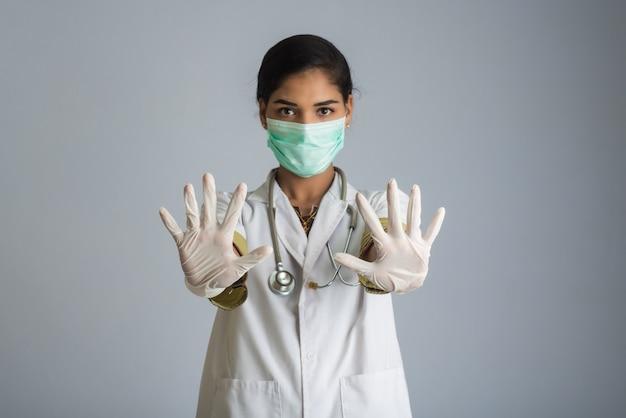 Jeune femme médecin portant un masque médical montrant le signe. femme médecin portant un masque chirurgical pour le virus corona.