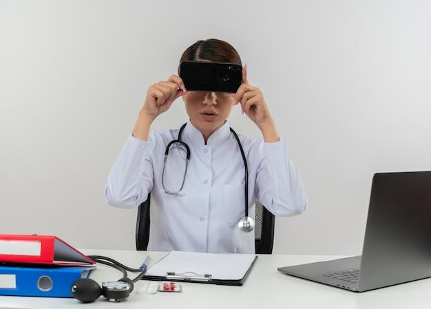 Jeune femme médecin portant une robe médicale avec stéthoscope assis au bureau de travail sur ordinateur avec des outils médicaux couverts yeux avec téléphone avec espace copie