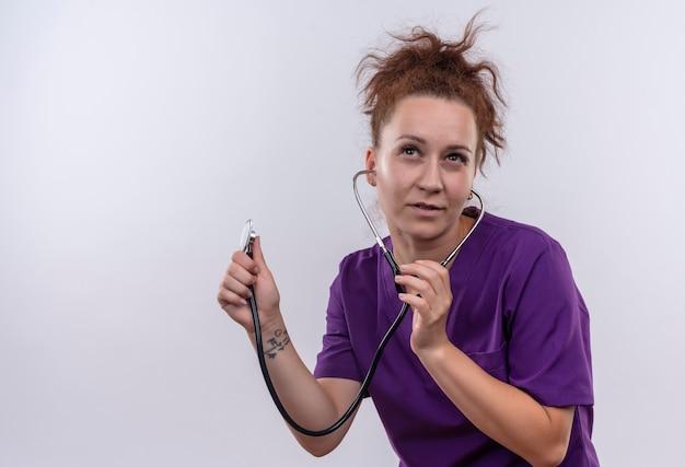 Jeune femme médecin portant l'uniforme médical à l'écoute de l'espace copie vide avec stéthoscope pensif debout sur mur blanc