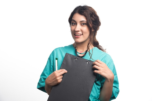 Jeune femme médecin avec presse-papiers tenant un stylo dans sa main sur fond blanc. photo de haute qualité
