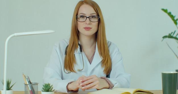 Jeune femme médecin professionnelle porter l'uniforme avec un stéthoscope par appel vidéo conférence