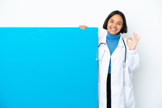 Jeune femme médecin de race mixte avec une grande pancarte isolée sur fond blanc montrant un signe ok avec les deux mains