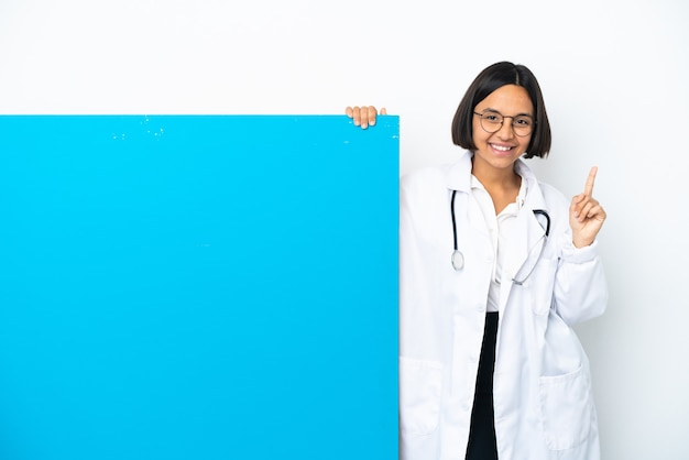 Jeune femme médecin de race mixte avec une grande pancarte isolée sur fond blanc pointant vers une excellente idée