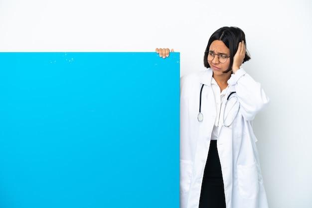 Jeune femme médecin de race mixte avec une grande pancarte isolée frustrée et couvrant les oreilles